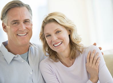 Mature smiling white couple sitting on couch