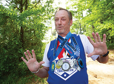 John Crosby showcasing various medals he's won at running events.