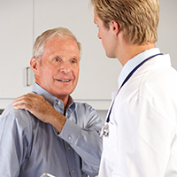 doctor with elder man holding shoulder