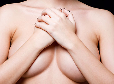 Women with arms covering bare breasts