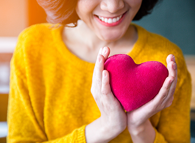 woman in yellow shirt holding heart pillow