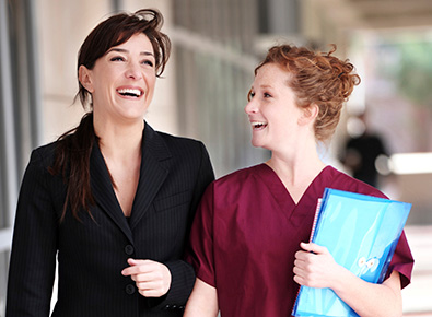 Photo of a nurse and another staff member talking and walking.
