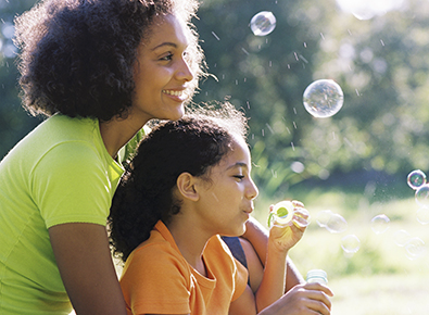 woman and daughter blowing bubbles