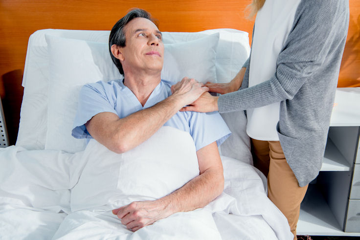 Man in hospital bed with visitor